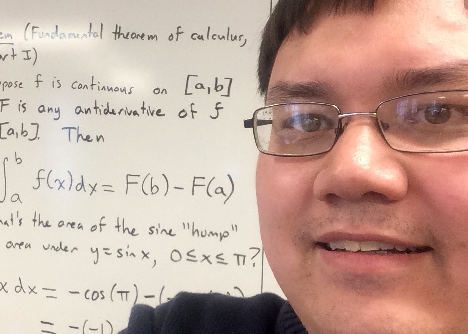 picture of Chris in  front of whiteboard with handwritten math