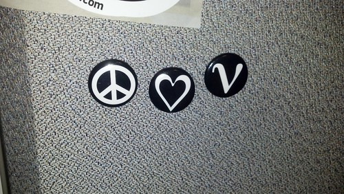 Buttons with peace symbol, heart, and Greek letter nu